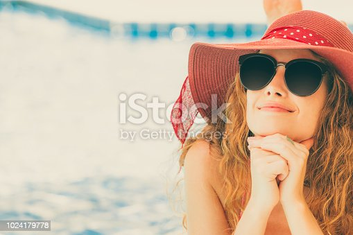 1062333060istockphoto Happy young woman in swimsuit at swimming pool. 1024179778