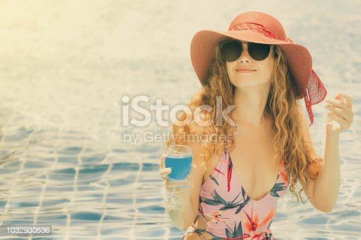 1062333060istockphoto Happy young woman in swimsuit at swimming pool. 1032930536