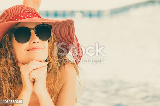 1062333060istockphoto Happy young woman in swimsuit at swimming pool. 1062332986