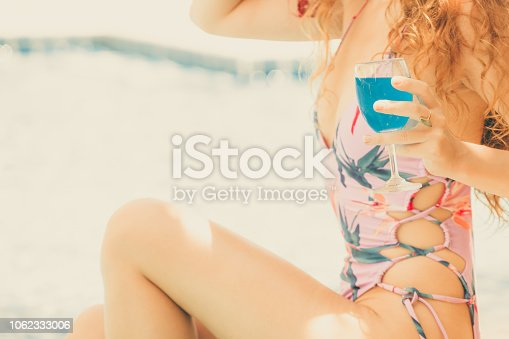 1062333060istockphoto Happy young woman in swimsuit at swimming pool. 1062333006