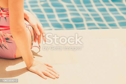 1062333060istockphoto Happy young woman in swimsuit at swimming pool. 1062333012