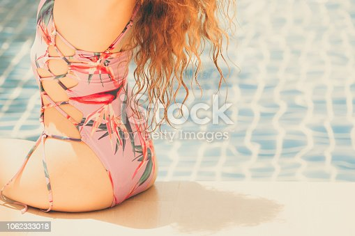1062333060istockphoto Happy young woman in swimsuit at swimming pool. 1062333018