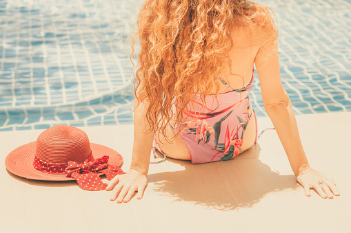1062333060 istock photo Happy young woman in swimsuit at swimming pool. 1062333028