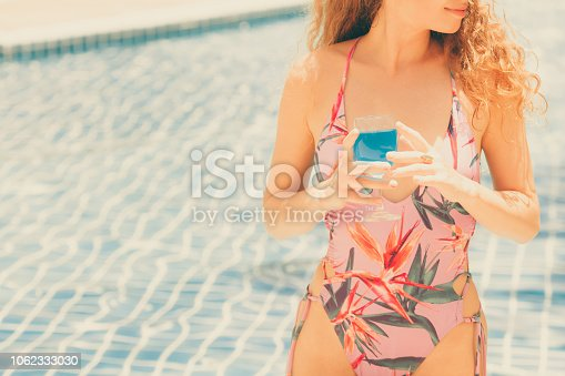 istock Happy young woman in swimsuit at swimming pool. 1062333030