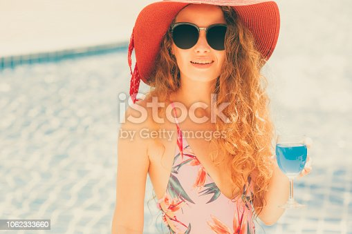 1062333060istockphoto Happy young woman in swimsuit at swimming pool. 1062333660