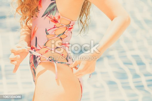 1062333060istockphoto Happy young woman in swimsuit at swimming pool. 1062334086