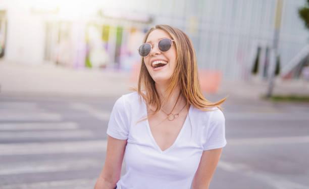 glückliche junge frau im stadt-portrait - sommer teenagermode stock-fotos und bilder