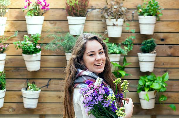 glückliche junge frau im garten - paletten terrasse stock-fotos und bilder
