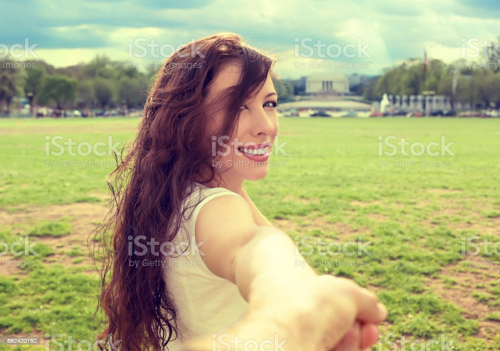 Happy young woman in Washington DC downtown extending you an arm inviting royalty-free stock photo