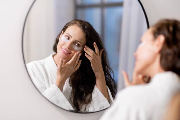 Glückliche junge Frau im weißen Bademantel setzen Undereye Patches auf Gesicht – Foto