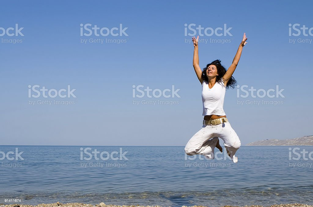 happy young woman is jumping in the beach royalty-free stock photo