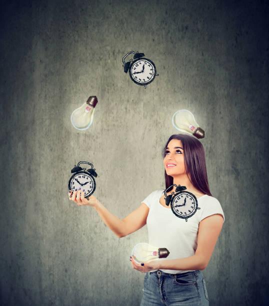 Glückliche junge Frau jongliert helle Glühbirnen und Wecker – Foto
