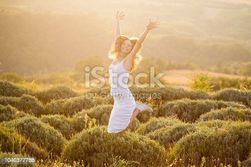 Happy young woman jumping in nature. About 20 years old, Caucasian brunette.