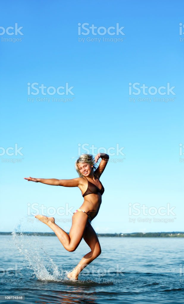 Happy young woman jumping in water royalty-free stock photo