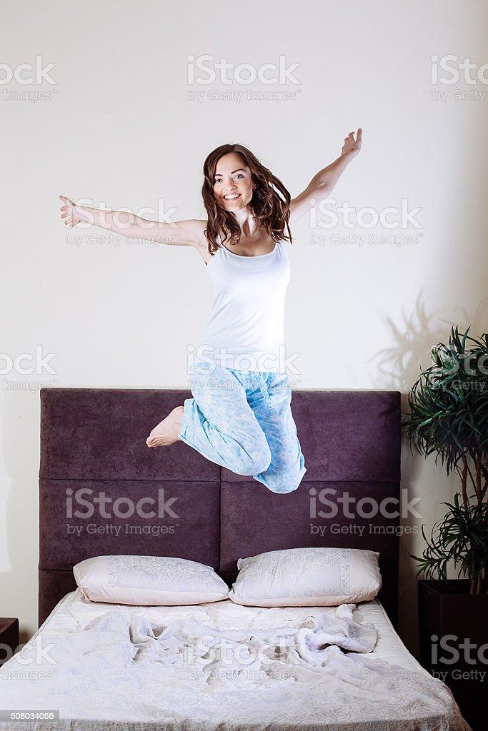 Glückliche junge Frau springt auf Bett – Foto