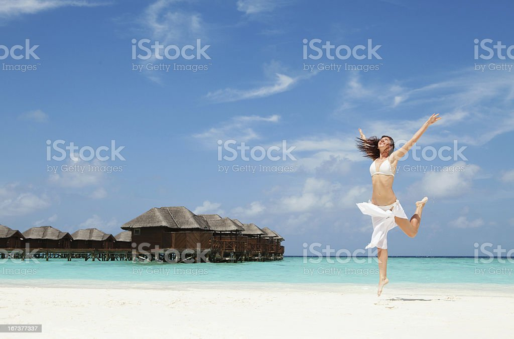 happy young woman jumping on the tropical beach royalty-free stock photo