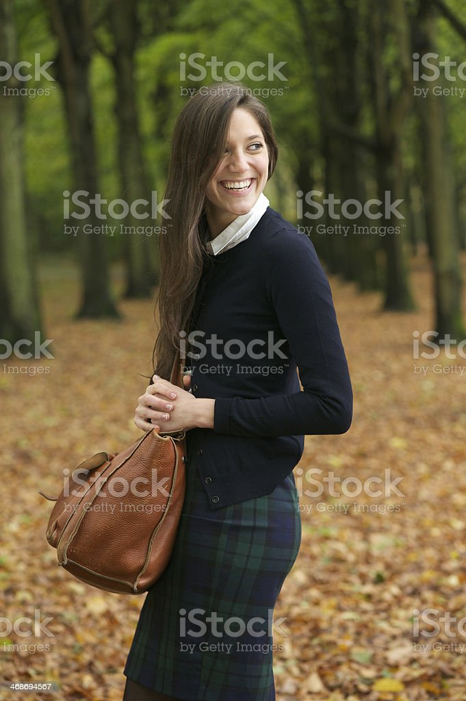 Happy young woman laughing and walking outdoors with bag royalty-free stock photo