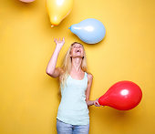 istock Happy young woman laughing with balloons 492500151