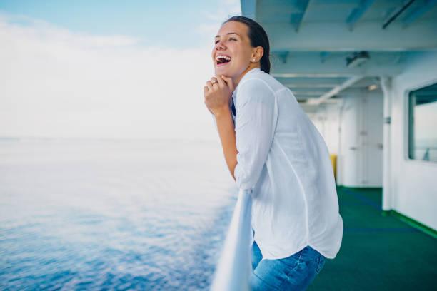 Glückliche junge Frau, die sich auf den Zaun des Boats stützt und das Meer beobachtet – Foto