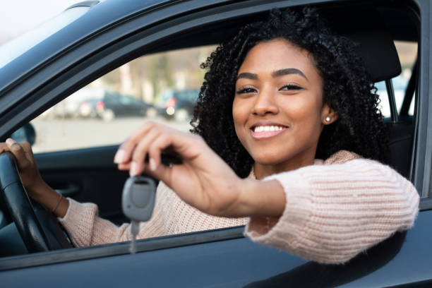Happy young woman learning to drive car Happy young black woman seated in her new car car key stock pictures, royalty-free photos & images