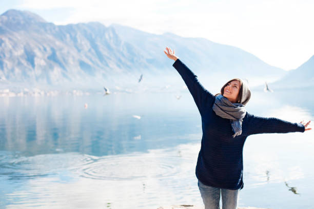 Happy young woman like flying seagulls at winter sea beach. Girl traveler smiling at amazing coastline stock photo