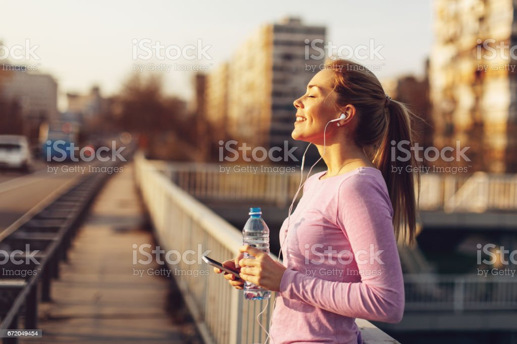 Happy young woman listening to music after jogging at sunset stock photo