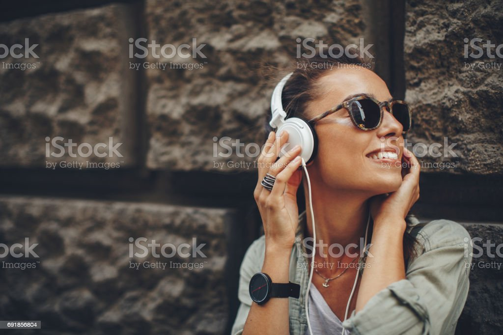 Happy young woman listening to music via headphones on the street on a sunny day stock photo