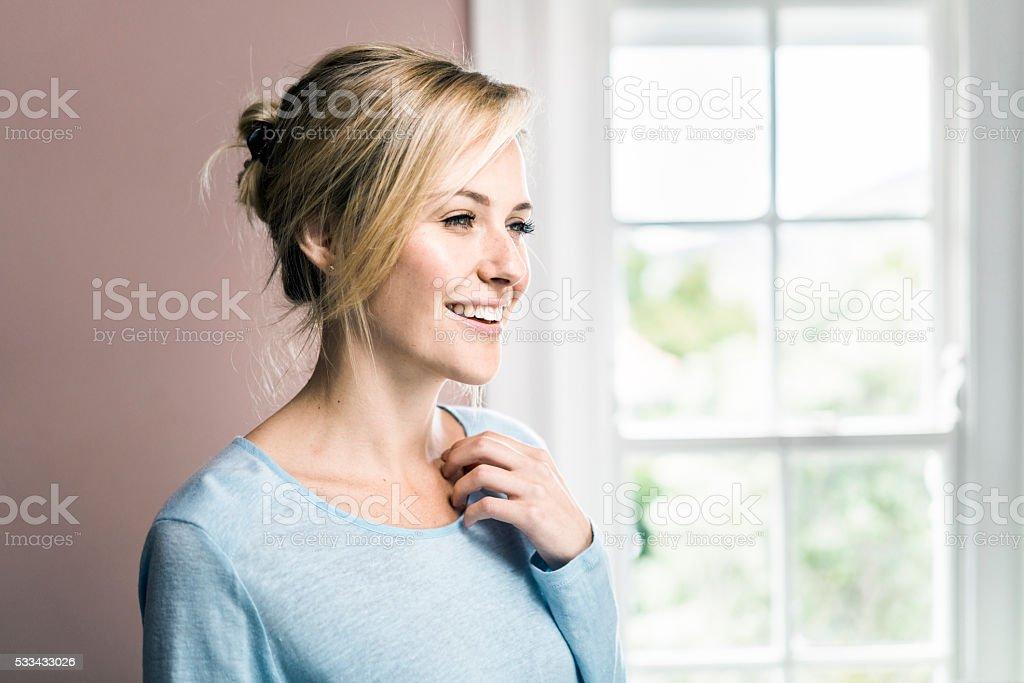 Jeune femme regardant dans bien éclairées maison - Photo
