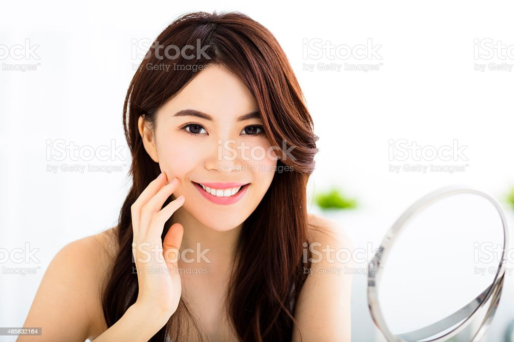Happy young woman  looking on mirror stock photo