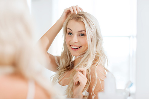 beauty, hygiene, hairstyle, morning and people concept - smiling young woman looking to mirror at home bathroom