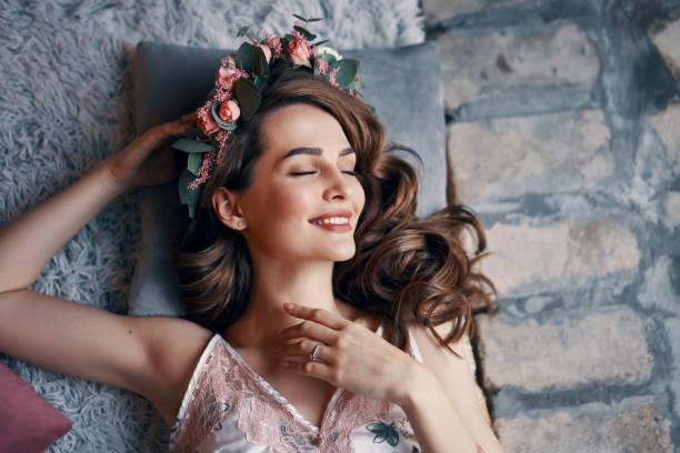 Mujer joven feliz acostada en la cama con los ojos cerrados después de despertar - foto de stock