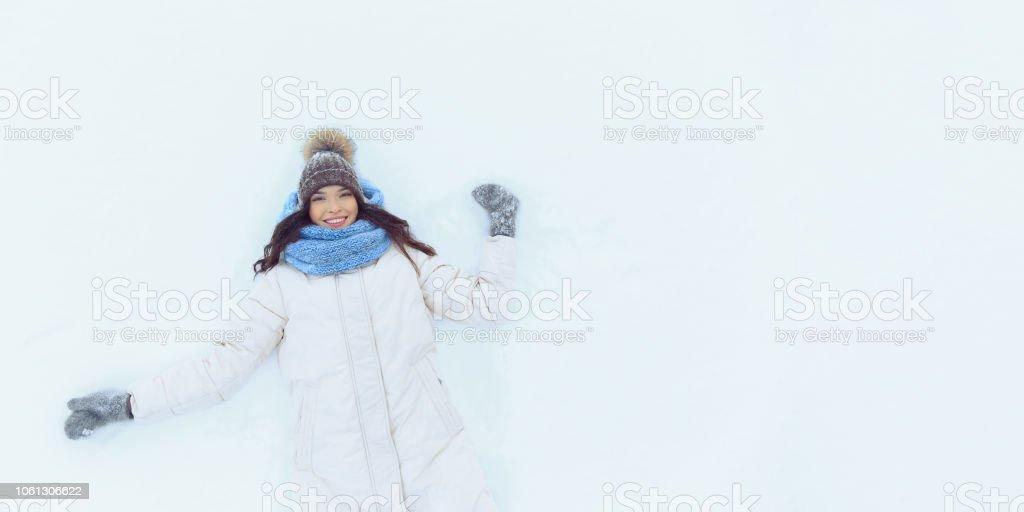 Glückliche junge Frau liegend auf Schnee im winter – Foto