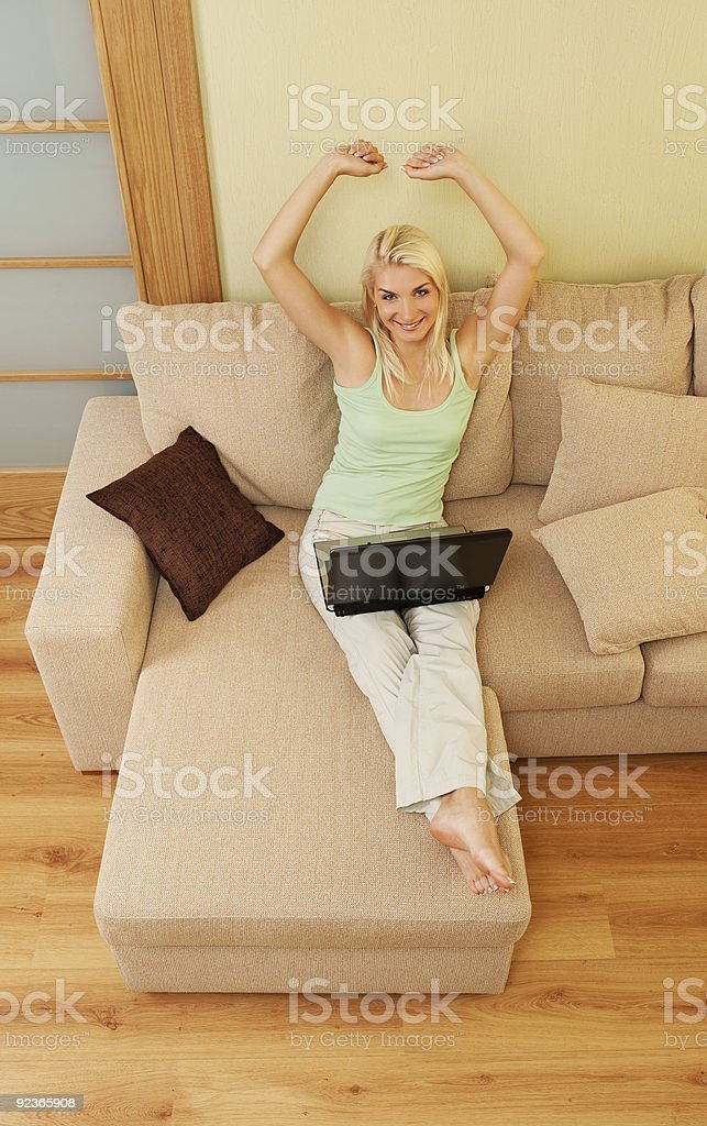 Happy young woman lying on sofa with laptop royalty-free stock photo