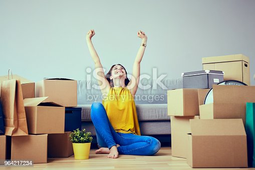 istock Happy young woman moving to new home - having fun 964217234