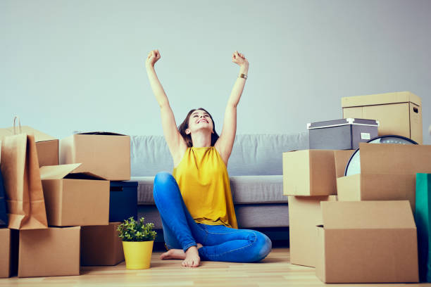 Happy young woman moving to new home - having fun Happy young woman moving to new home - having fun adult student stock pictures, royalty-free photos & images