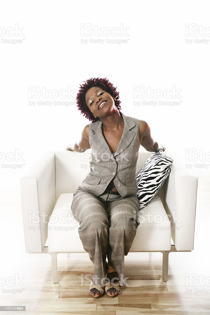 Happy young woman on an armchair royalty-free stock photo