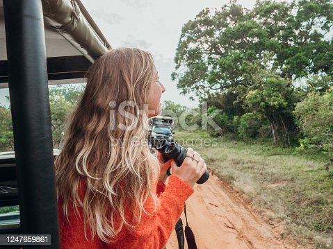 Happy young woman on luxury safari searching for wild animals in the jungle using binoculars. Girl in moving vehicle 4x4 looking for wildlife in national park