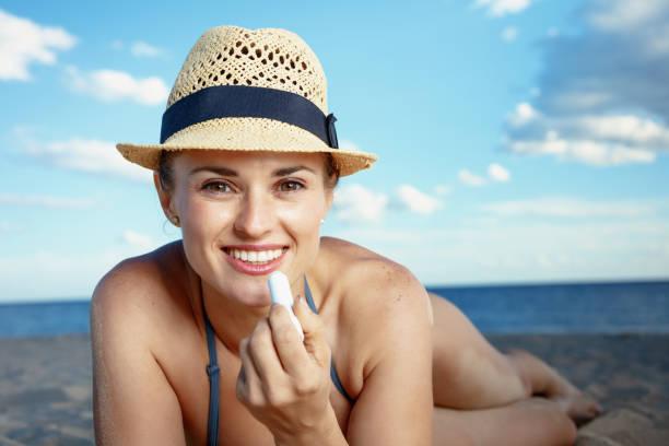 glückliche junge Frau am Ufer des Meeres, die Sonne Schutz Lippenstift – Foto
