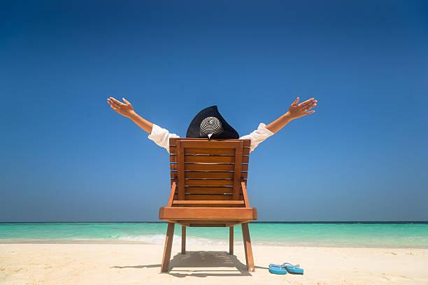 glückliche junge frau am strand - sun chair stock-fotos und bilder