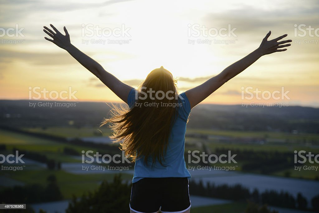 happy young woman outdoor rising hands looking landscape on sunset stock photo