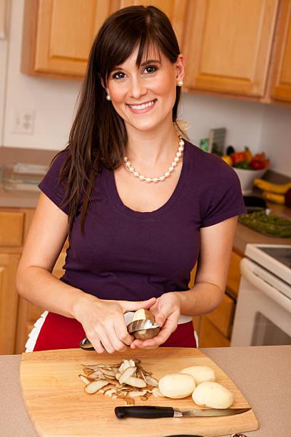 glückliche junge frau schälen kartoffeln in der küche - peeling zu hause machen stock-fotos und bilder