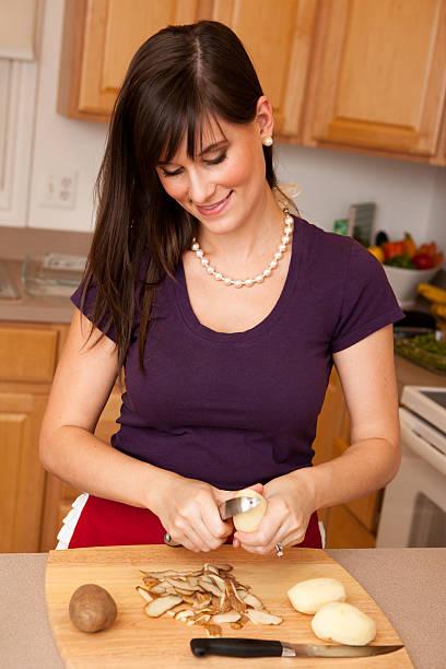 glücklich jungen frau schälen kartoffeln in der küche - peeling zu hause machen stock-fotos und bilder