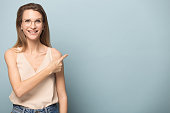 istock Happy young woman pointing on blank copy space for text. 1162203111
