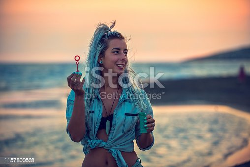 Happy young woman portrait blowing soap bubbles