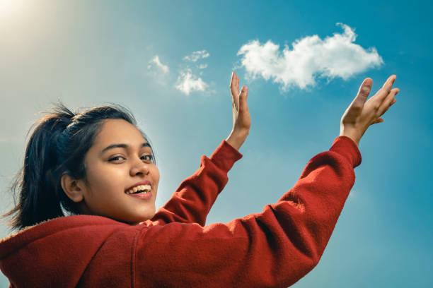 Glückliche junge Frau posiert vor der Kamera, wie sie die Wolke hält. – Foto