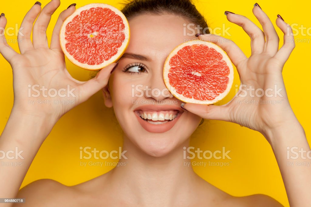 Happy young woman posing with slice of red grapefruit on her face on yellow background royalty-free stock photo