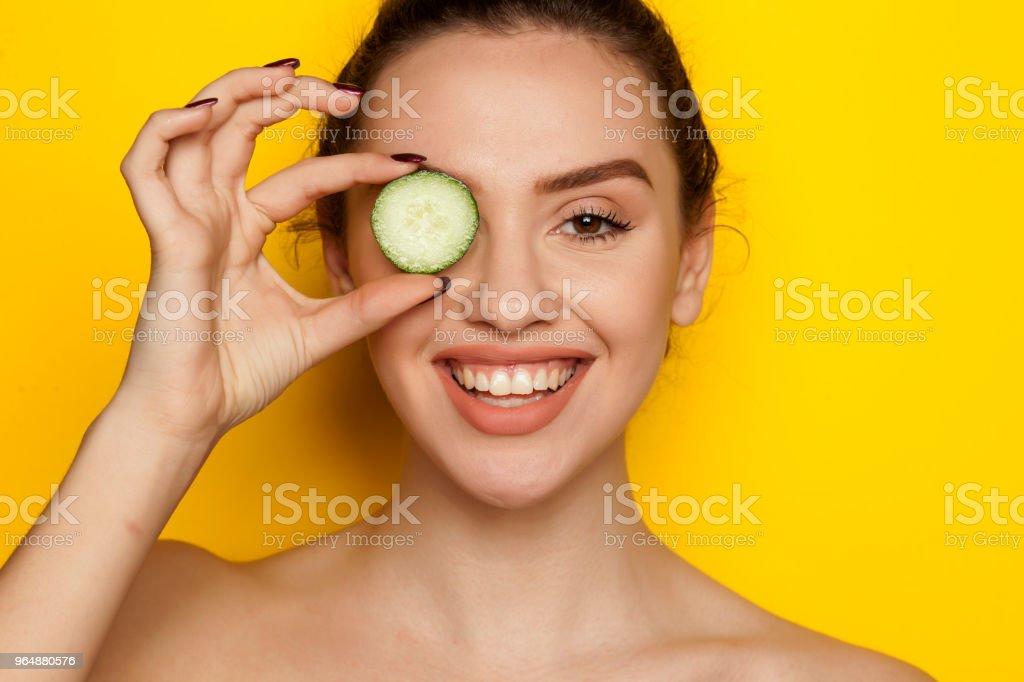 在黃色背景下她的臉上擺著黃瓜片的快樂少婦 - 免版稅一個人圖庫照片