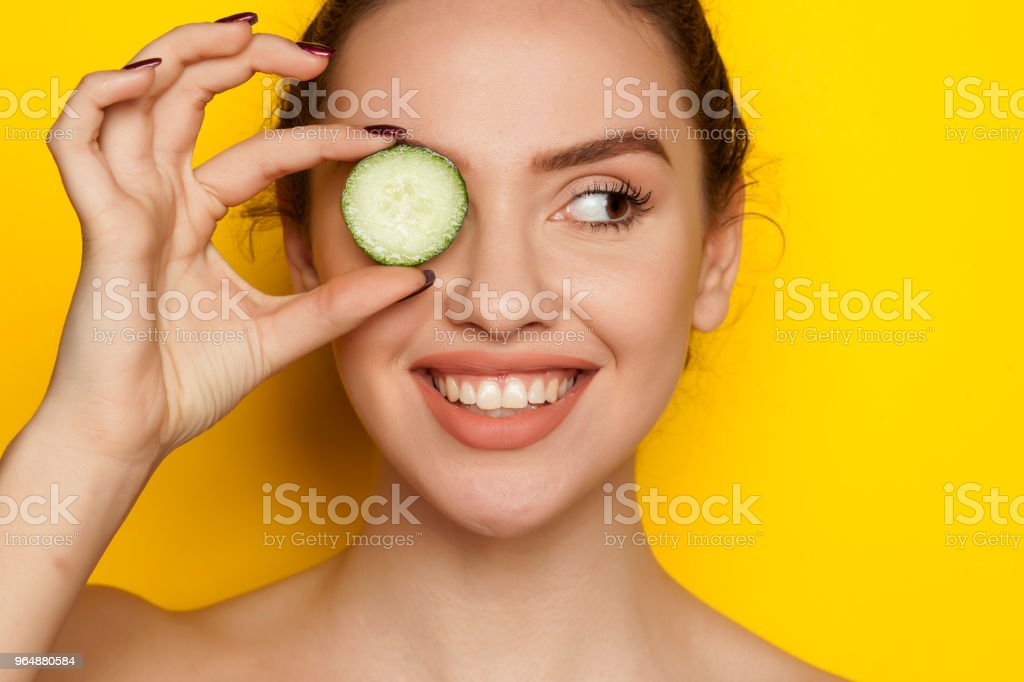 Happy young woman posing with slices of cucumber on her face on yellow background royalty-free stock photo