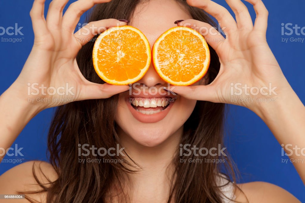 Happy young woman posing with slices of oranges on her face on blue background royalty-free stock photo