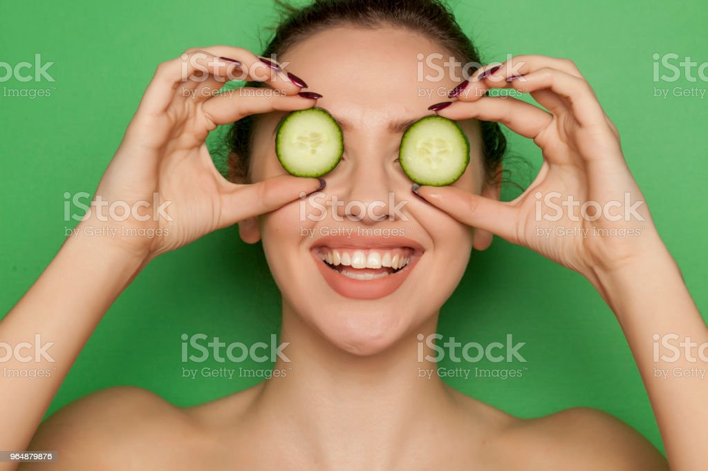 Happy young woman posing with slices of oranges on her face on green background royalty-free stock photo